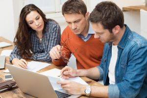 Businessmen and businesswoman working with document in office